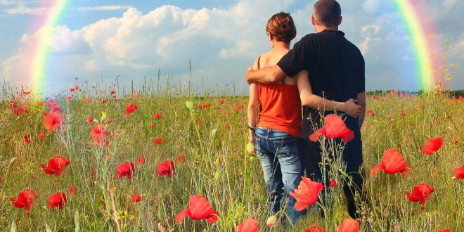 a couple in a field looking toward a rainbow